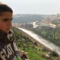 Gibreel Burnat devant le mur de la honte en Cisjordanie occupée